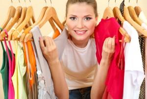 En glad dame ved en knagrække af tøj
